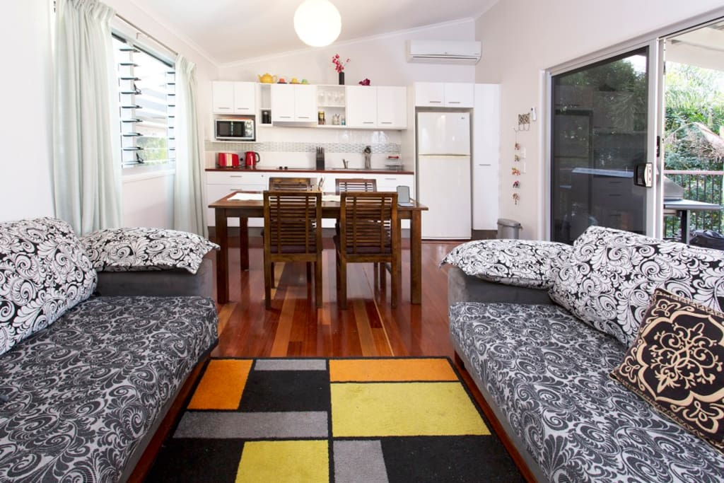 Full kitchen and indoor dining with fan and airconditioner and screened doors and windows