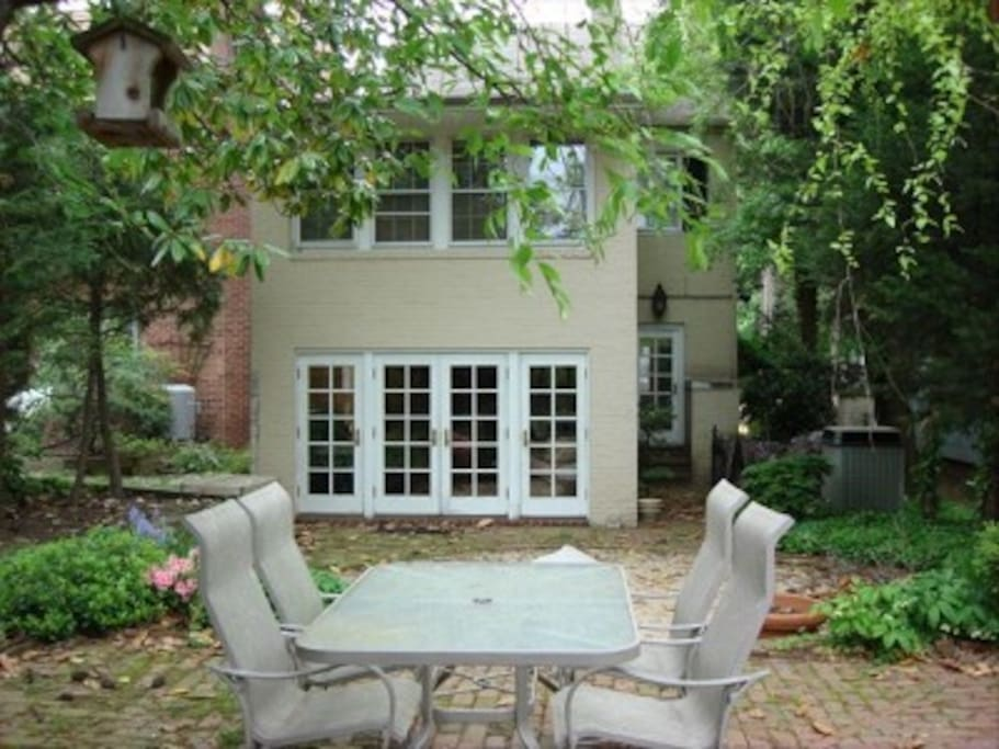 Lush, private backyard with brick patio and firepit