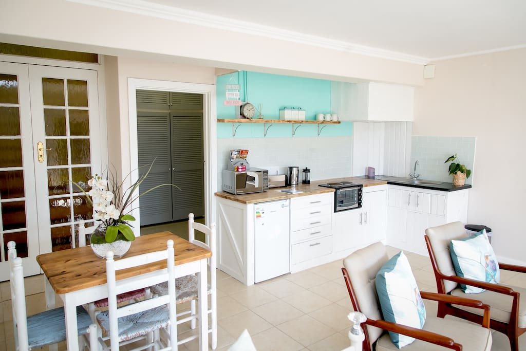 Our self catering kitchen, which always includes water, milk, orange juice, tea, coffee, sugar, eggs, biscuits and a bottle of champers/beer to welcome you!   We also have a fab dining table for you to sit indoors and have breakfast etc.