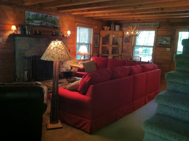 Enter into the comfortable living area with plenty of seating in front of stone woodburning fireplace and HD TV