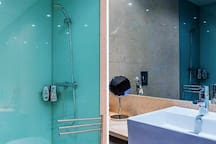 Shower bathroom with hair dryer and large spaces.