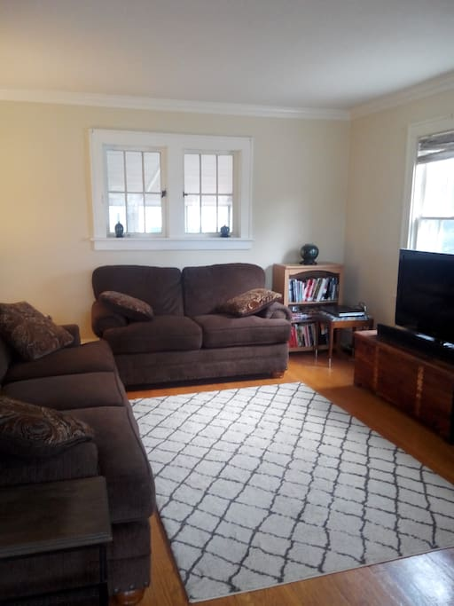 Living room with flat screen TV. Comfortable couch for lounging or sleeping.