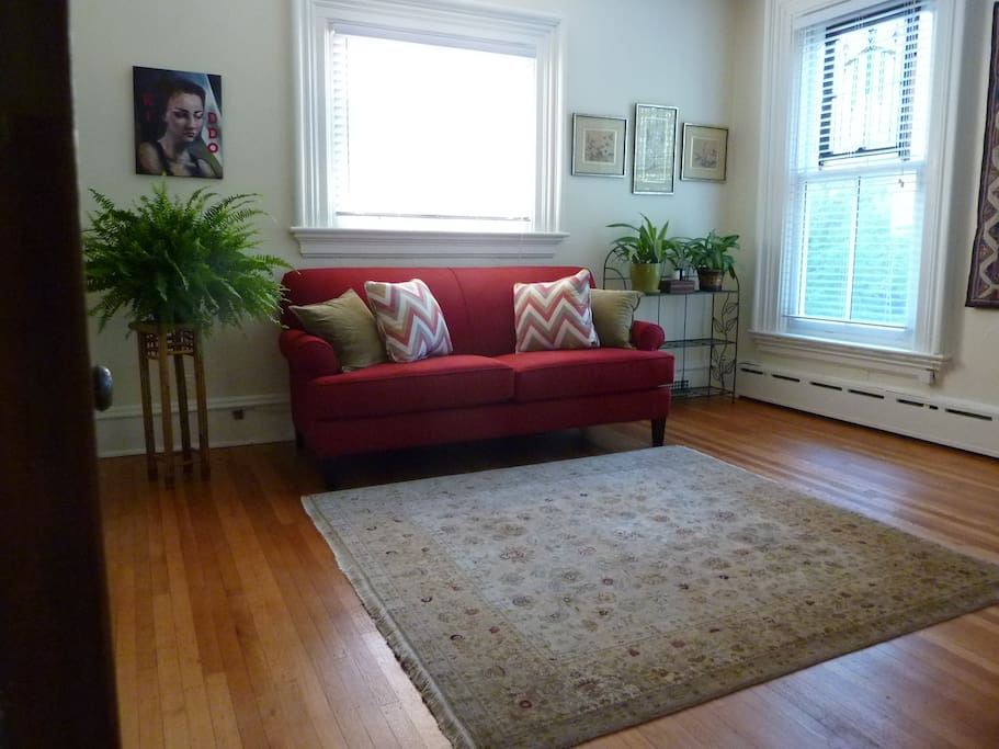 Spacious living room with original hardwood floors.