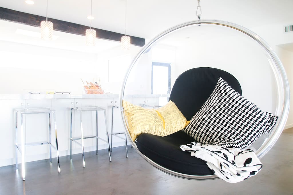 Classic bubble chair with kitchen island and extra seating in the background