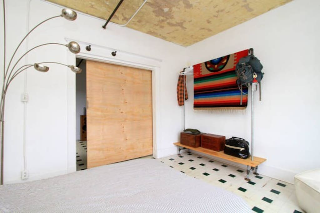 Custom sliding door for privacy, Hand built industrial clothing hanging.