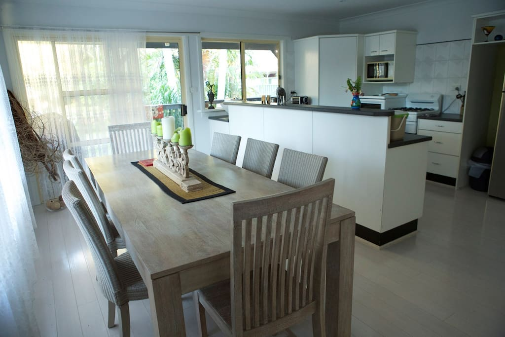 Large dining area and a fully self contained kitchen looks out onto the large back wooden deck and backyard.