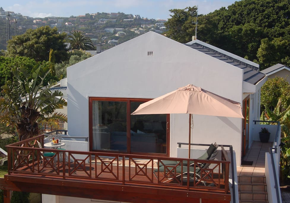 Outside view of the upstairs apartment and sundeck. Includes 2 sun lounges, table and chairs and weber braai