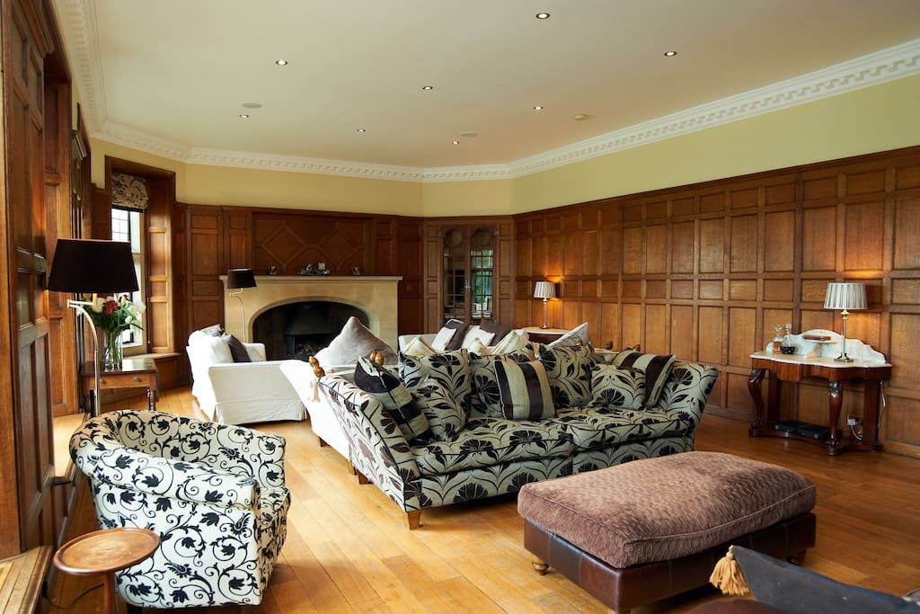 Oak panelled drawing room with plenty of comfy sofas