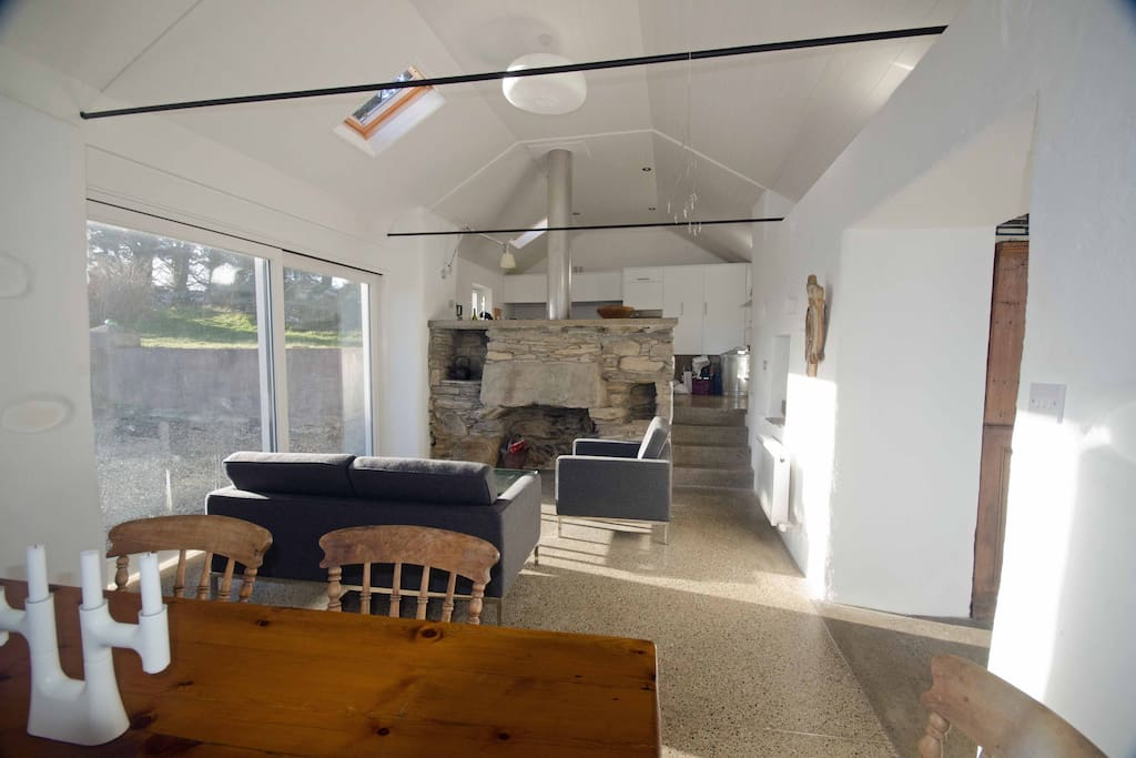 Kitchen/dining with wood burning stove and patio doors onto terrace with views and BBQ