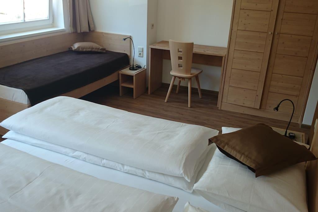 Eines der 2 Doppelzimmer im Appartement. Es bietet Platz für 3 Personen. 1 Doppelbett und ein Einzelbett. Schrank und Schreibtisch sind auch vorhanden.