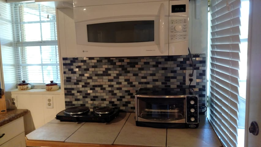 Convection Microwave, refrigerator, toaster oven, hot plate, coffee maker in kitchen.