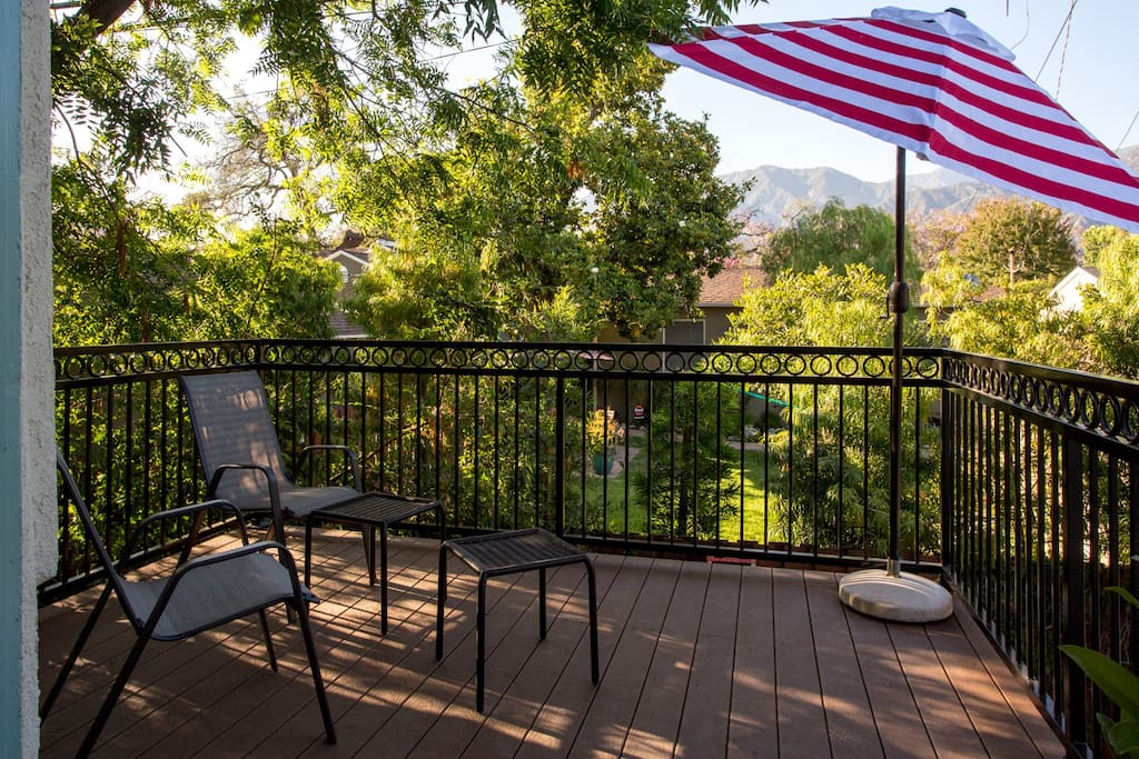 A spacious sun deck, surrounded by trees, with a spectacular view of the Angeles Crest - San Gabriel mountains.
