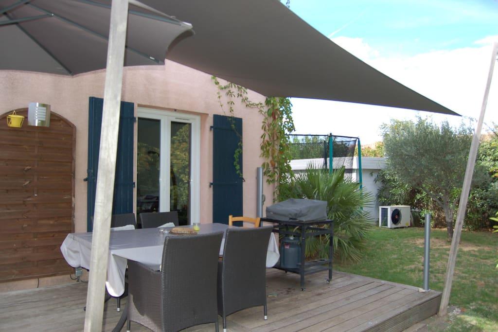 Terrasse pour les repas avec voile d'ombrage et plancha
