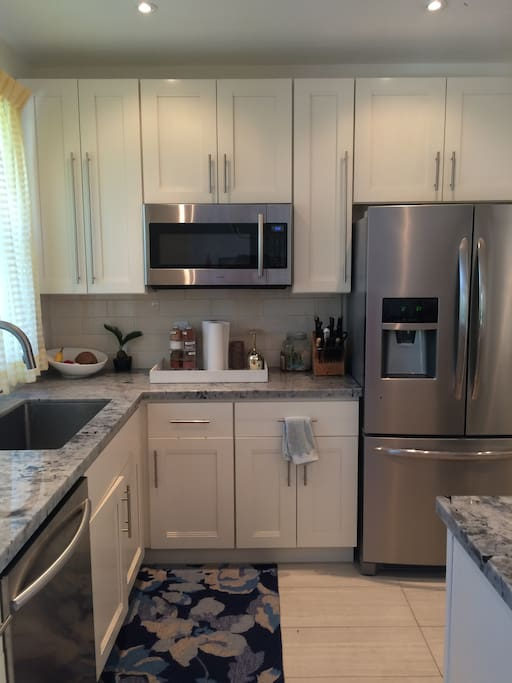 New kitchen with farmhouse sink and stainless steel appliances, cookware, pots and pans,