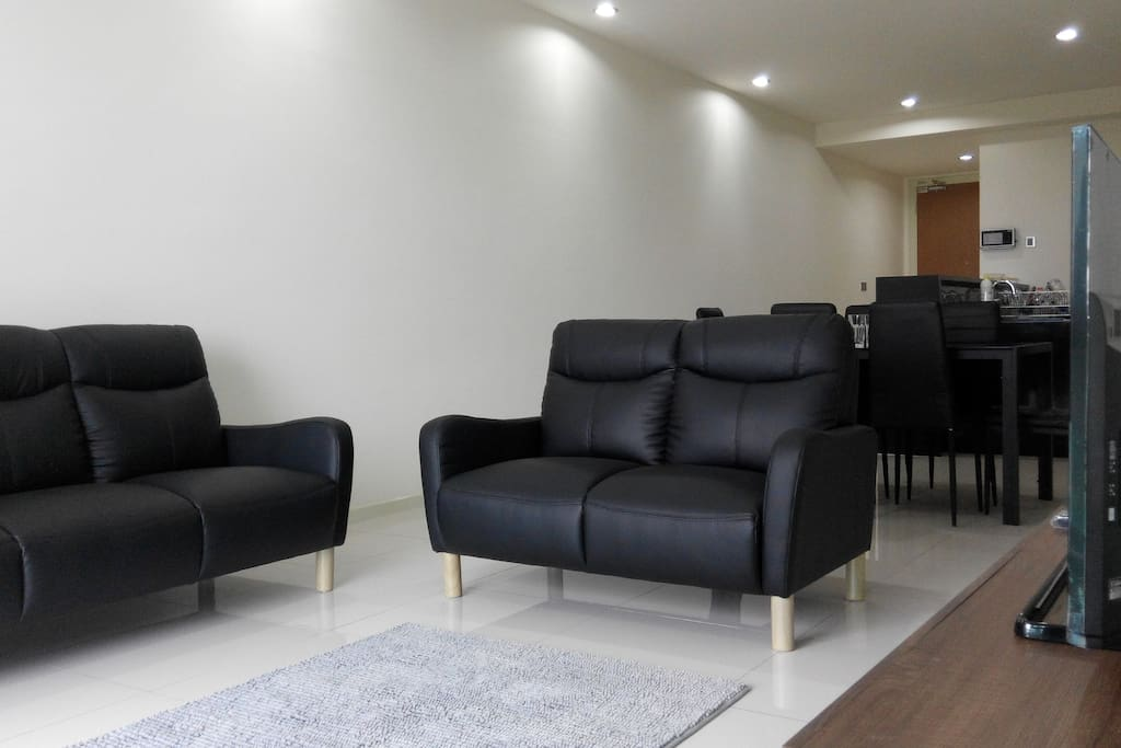 Living room with 2 and 3-seater couches, internet TV and adjacent dining area