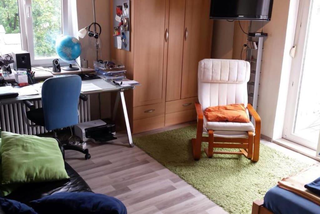 2 große Fenster sorgen für ein helles, freunliches Licht im Raum. Sessel, Schreibtischstuhl und Couch bieten bequeme Sitzmöglichkeiten. An der Wand ist ein TV befestigt der zu Couch oder Bett gedreht werden kann.