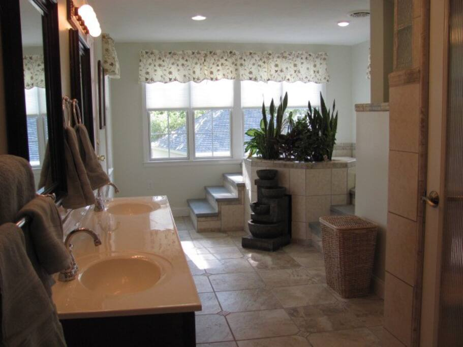 Ceramic tiled Master bath with Jacuzzi tub ; Steam room and two person shower with body jets; Double sink vanity and lit mirrors .
