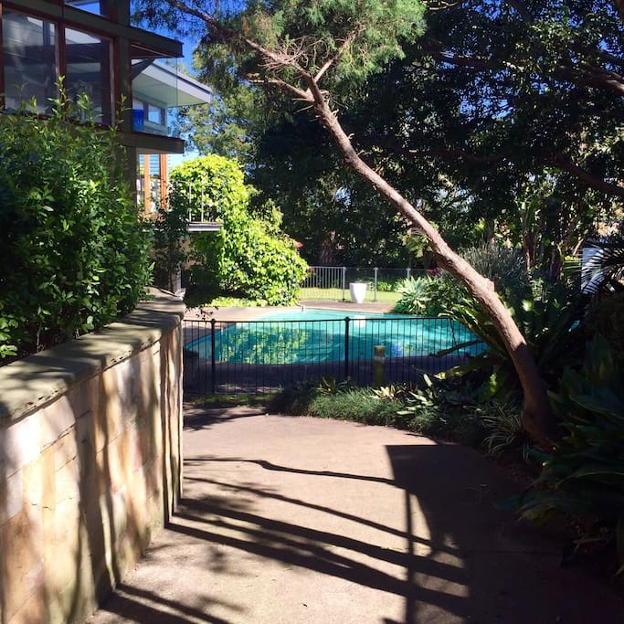 Enter via wooden side gate and walk down path towards pool, apartment is on left