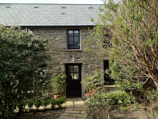 The Cottage has original stone walls and is set in mature gardens