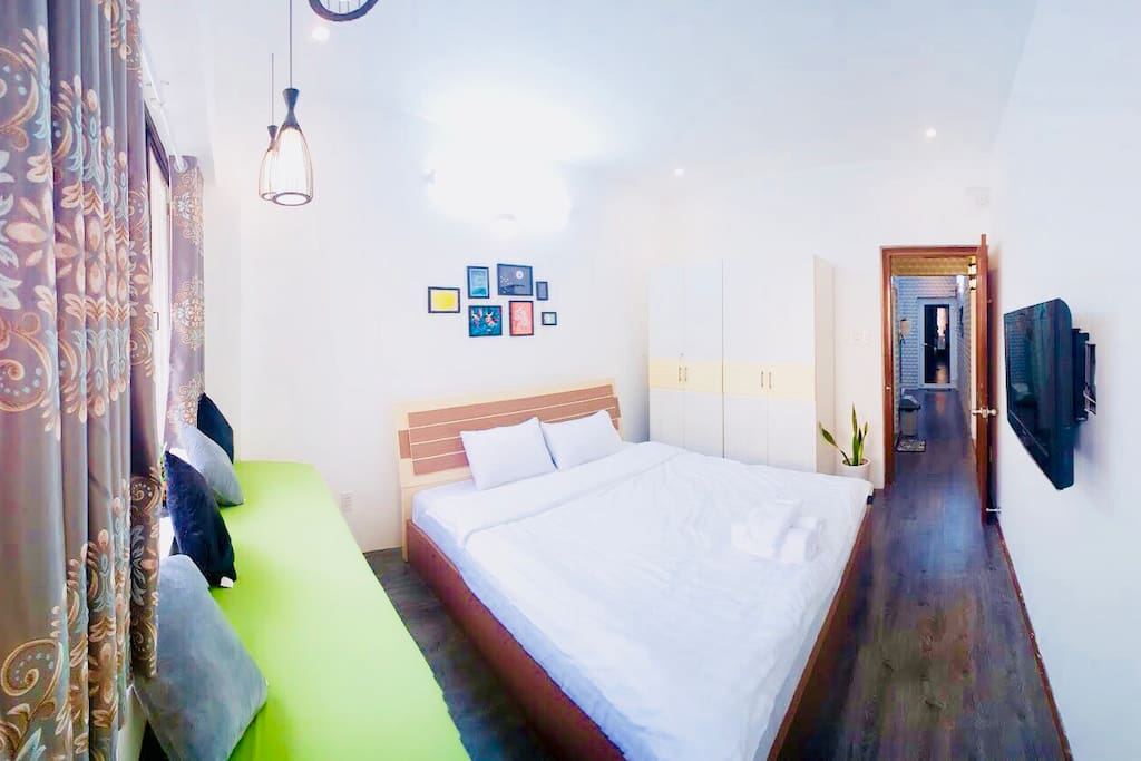 Bedroom with comfortable kingsize bed, good AC, cable TV and a sofa to sit with balcony view.