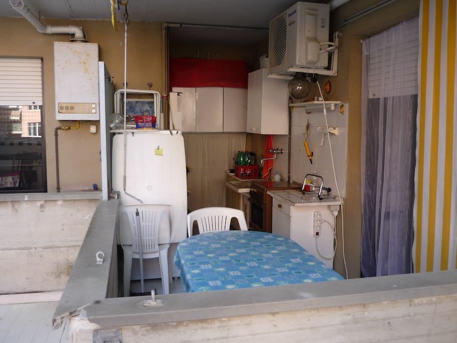 Terrazzo con tavolo, frigo, cucina e dispensa.