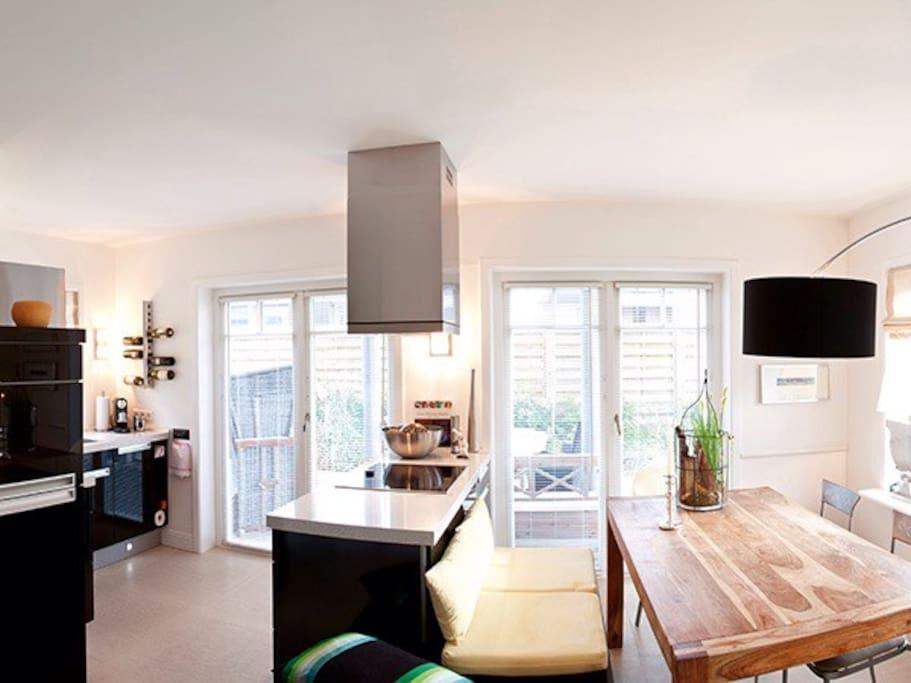 Herrlich praktisches Erdgeschoss mit gut ausgestatteter Küche und Fernseher sowie Blick auf die Südterrasse mit Garten.