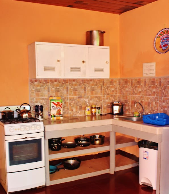 Shared kitchen with plates, pots, pans and cutlery.