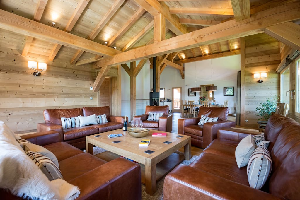 Large open plan living area with comfy sofas, log fire & fabulous views