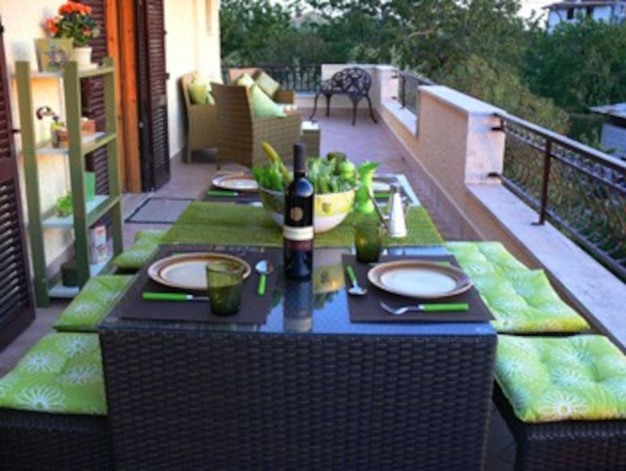 The outdoor terrace with dining and seating area and views down over the surrounding countryside.