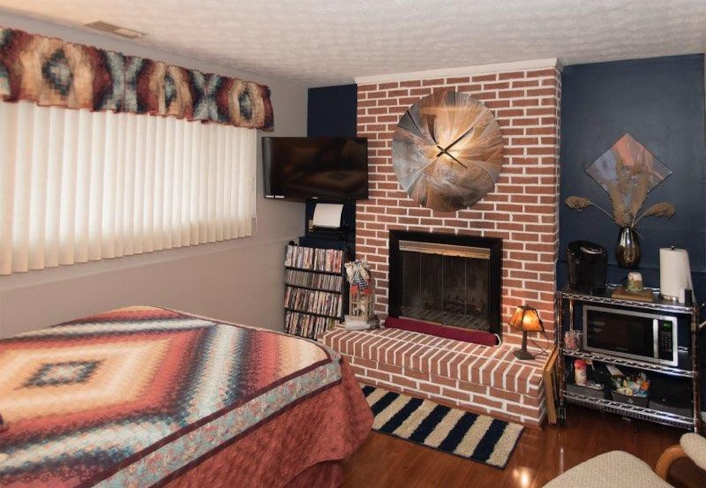 When entering the house, down the 1/2 flight of stairs & to immediate left is this warm & cozy space w/queen bed, TV, fireplace, microwave & coffee cart w/snacks & all the coffee fixings. The half bath & office area are in this space & to the right.