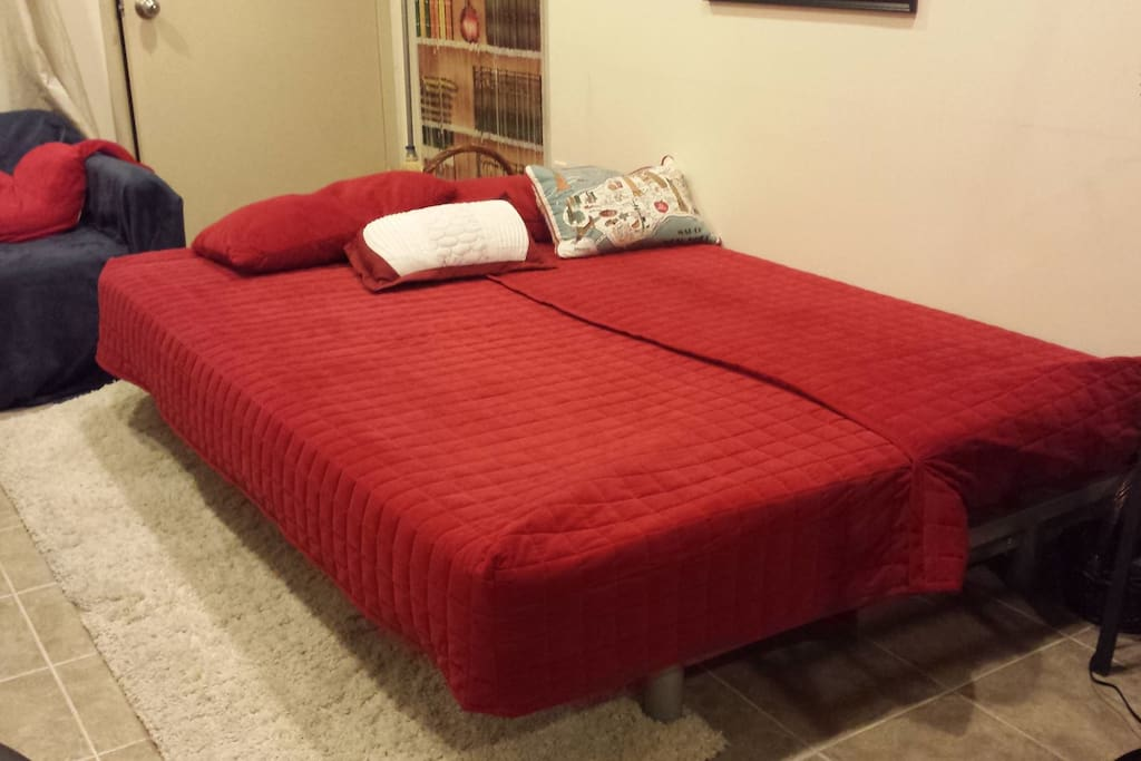This futon in the living room unfolds into a full-sized bed, enough to fit 2 people.