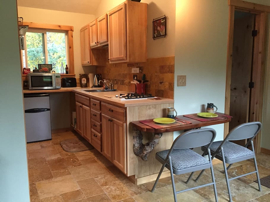 Kitchen area.  A tea selection and coffee is provided.  Frig, stovetop, microwave, dishes and cooking utensils on hand.  No oven.