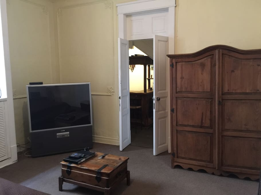 View from bed of armoire, large TV and entryway