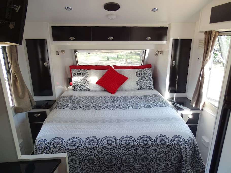 queen size bed with side tables and windows all around