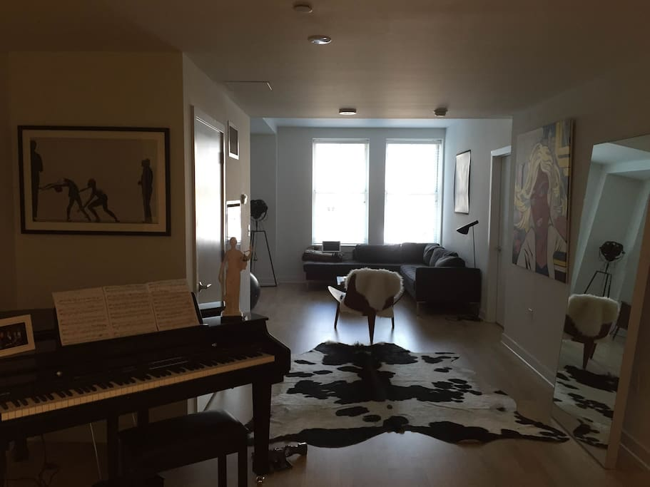 Well appointed large living room with baby grand piano.