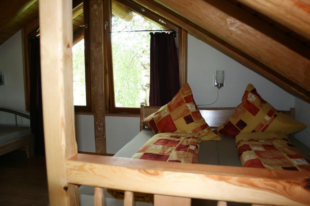 Schlafen unterm Dachstuhl aus Naturstämmen.