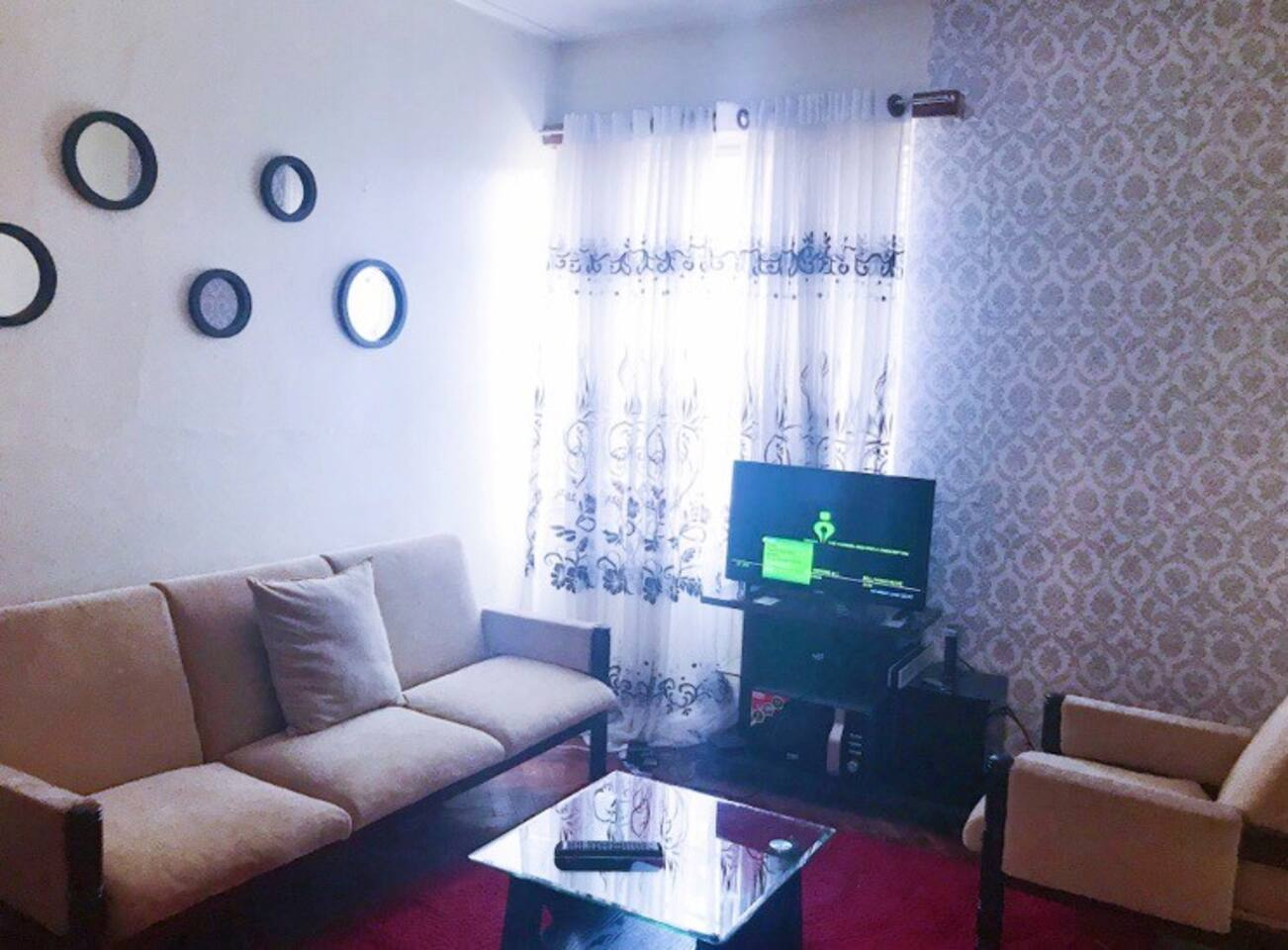 Well lit living room space that is comfy and airy. It has wooden floors and a fluffy carpet that keeps the place warm during cold seasons. Has cable tv with upto 62 channels and fast WIFI.