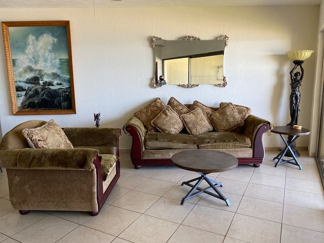 Couch and arm chair in living room. Coffee table and two end tables. This couch is also a pull out sofa bed.