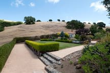 Pétanque court, rolling golden hills (waiting for you to hike), blue sky, green lawns.