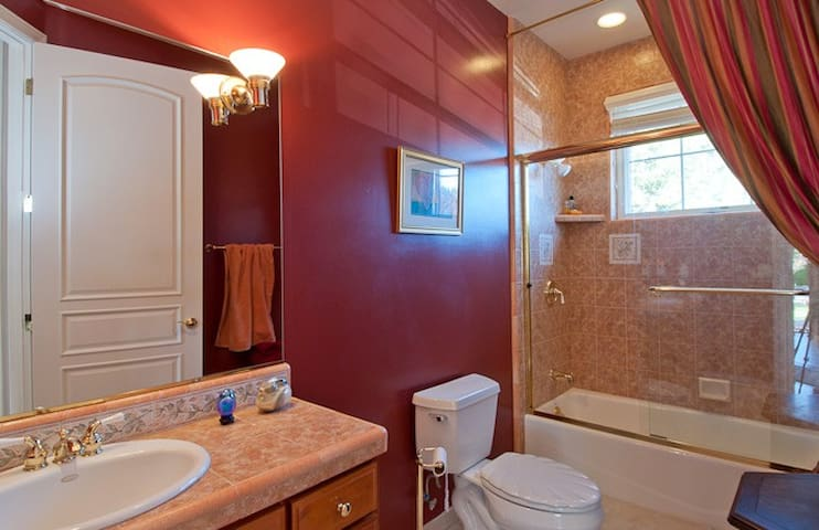 The two bedrooms share a bathroom. There is a tiled vanity and the shower over tub has a glass enclosure and a high window for natural light.