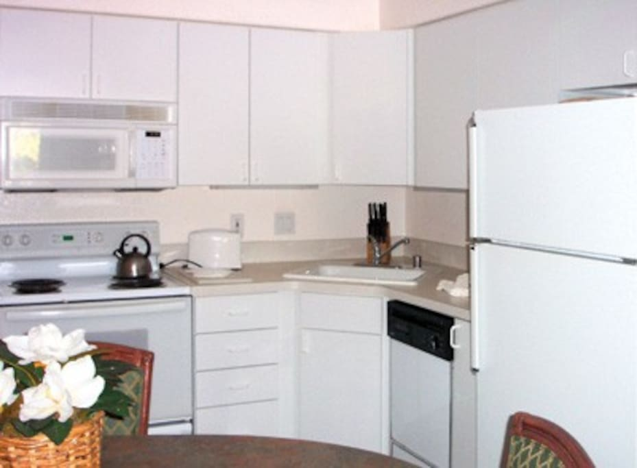 Compact kitchen, the unit we are renting has countertop burners, no oven. Coffee maker, toaster, blender, dishes, utensils, pots, etc. provided. W/D available at no cost, close by but not in unit.