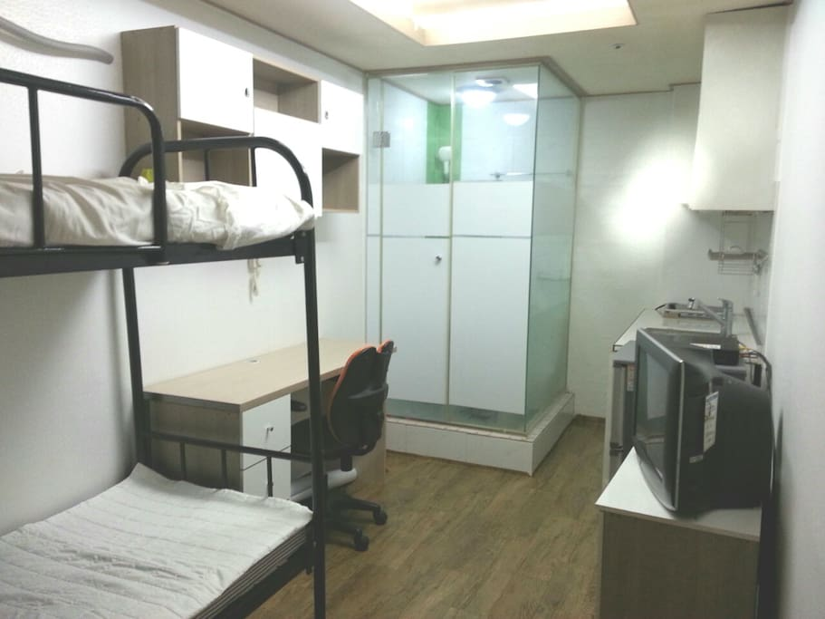 Double room overview including bed/TV/shower booth/fridge etc
