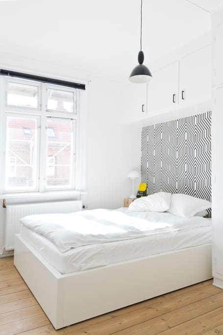Cosy double bed in a light and calm bedroom