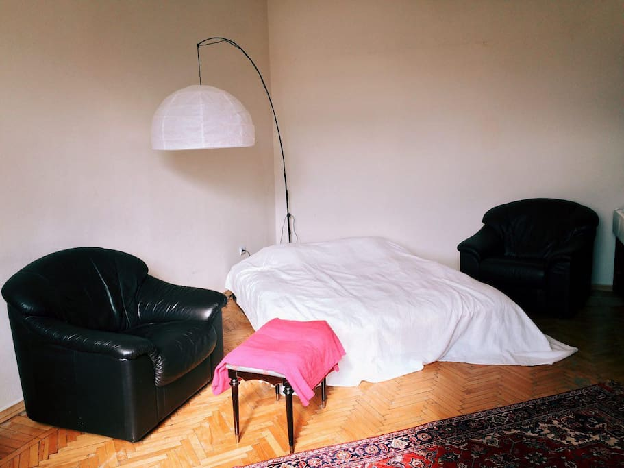Rest'n'sleep section with very comfortable bed, two black leather armchairs and Mis-Van-der-Rohe-style floor lamp