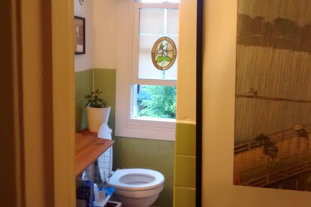 Washroom with full tub and stained glass.