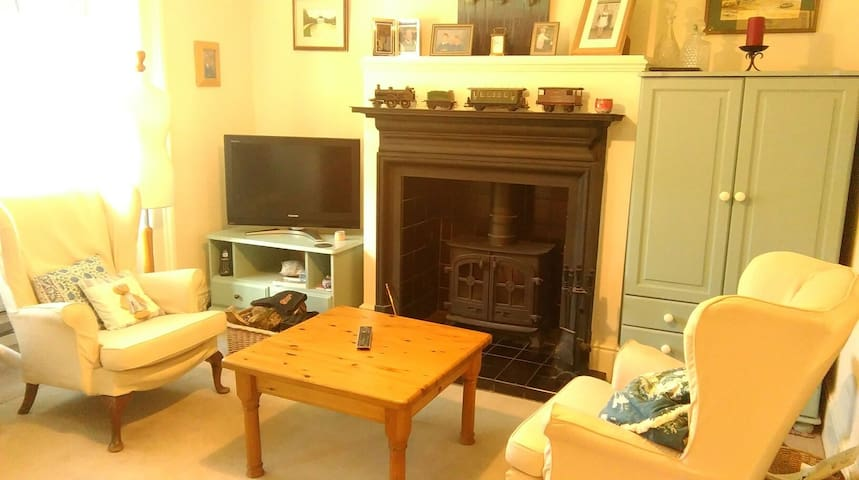 Cosy sitting room with TV and log burning stove.