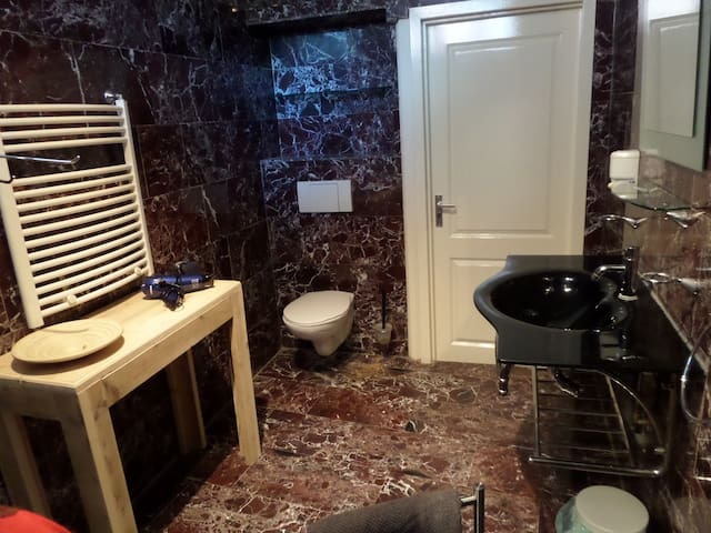 The bathroom with the toilet and bathroom sink. The side-table with hairdryer and heater.