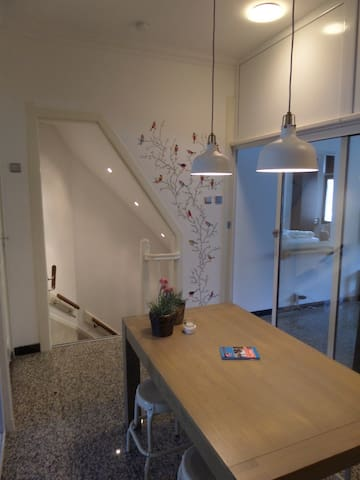 The kitchen with dinnertable for four, stairwell to the ground floor and on the right the entrance of the room..