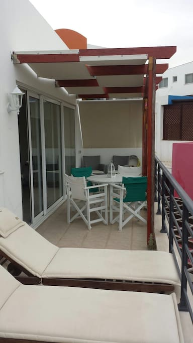 Terrace with loungers and dining area. Terrace spans entire apartment with double doors in the bedroom and in the lounge/kitchen