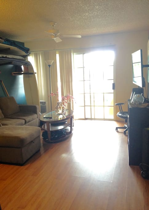 Living room with surf board racks and access to backyard